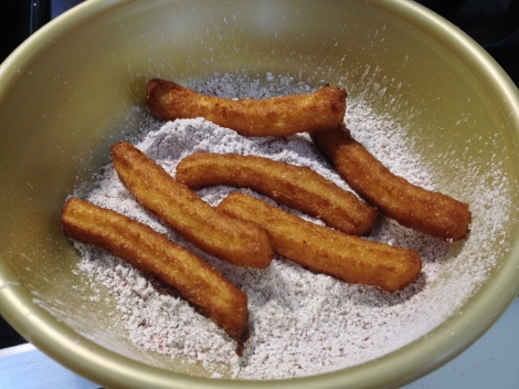 toss the churros in a bowl of sugar and cinnamon